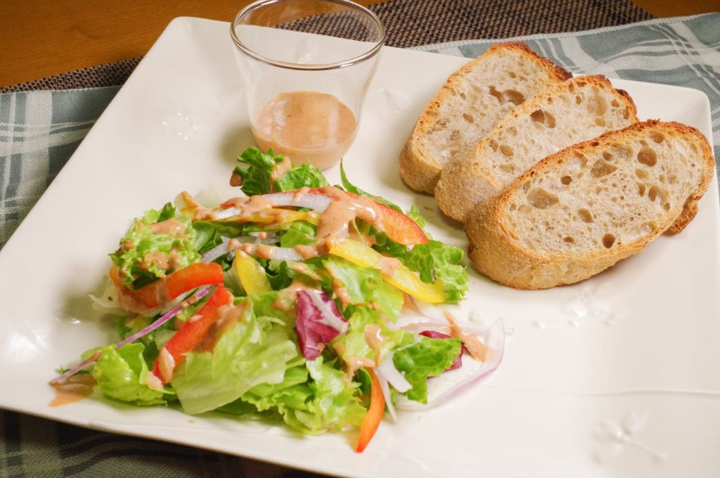 コオロギパンとコオロギパウダードレッシングがかかったサラダ